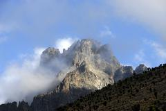 rocky mountain summit batian (5199 m) surrounded by clouds mount kenya nation - stock photo