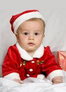 a little boy, 9 month old, in the disguise of santa claus - stock photo