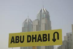 u.a.e., dubai, yellow traffic sign shows how to turn in direction to abu dhab - stock photo