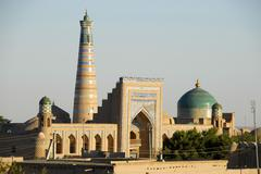 high minaret of islom xo\'ja madrasah and big blue cupola of pahlavon-maxmud- - stock photo