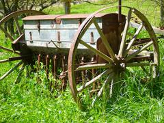 old wooden and rusty iron barrow suspended in grass - stock photo