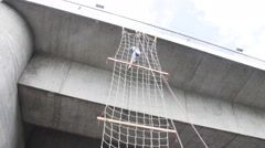 Stock Video Footage of Climbing and down a rope ladder attached to the bridge