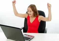 Stock Photo of exultant woman using laptop