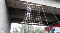 Stock Video Footage of Climbing rope ladder attached to the bridge