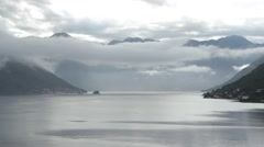 Cloudy sky above rocky mountains. Seascape with hills and water. Panoramic view. - stock footage