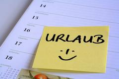 """yellow reminder note """"urlaub"""" (holiday) on the page of a calendar - stock photo"""