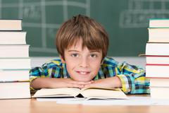 Young boy in school surrounded by textbooks Stock Photos