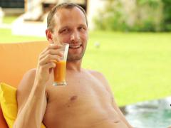 Hansome man relaxing with drink on sunbed NTSC Stock Footage