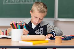 little boy doing artwork at school - stock photo
