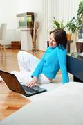 Young woman at home using laptop Stock Photos