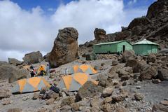 Tents huts and big rocks school hut kikelewa route kilimanjaro tanzania Stock Photos