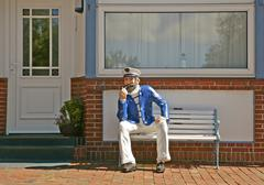 life-size figure of a seaman sitting on a bench - stock photo