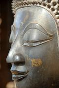face of a bronze buddha statue temple museum of art and antiquities haw pha k - stock photo