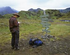 woman studies map in front of a guidepost, thorsmoerk, iceland - stock photo