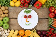 healthy eating smiling face from vegetables on plate - stock photo