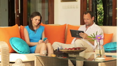 Couple with smartphone and tablet sitting on sofa at home HD Stock Footage