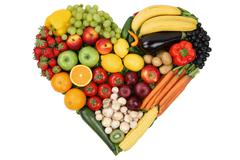 Fruits and vegetables forming heart love topic and healthy eating Stock Photos