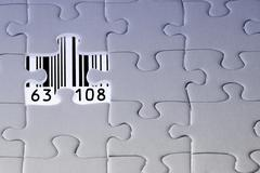 Jigsaw puzzle, the last missing piece revealing a barcode with numbers Stock Photos