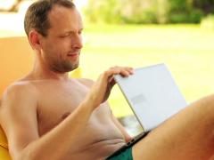 Man with laptop having a break on sunbed by the pool NTSC Stock Footage