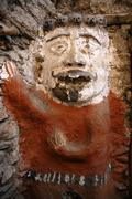 Old white and red painted male figure at a city gate of boen animist belief k Stock Photos