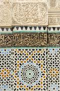 artful wall with colourful glazed tiles and stucco medersa bou inania fes el- - stock photo