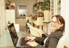 Young business woman using laptop at home Stock Photos