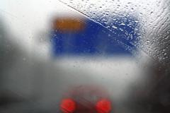Look through wet windscreen on blurred blue sign board and back lights on an  Stock Photos