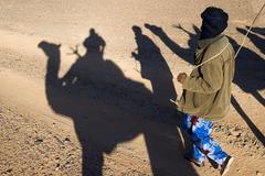 Shadow play, tuareg noamd and shadows cast by the dromedaries of a caravan, a Stock Photos