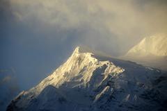 Snow-capped peak in the mornig mist near manang annapurna region nepal Stock Photos