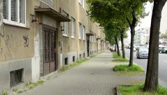 Urban street with road - buildings (flats) - trees and pavement - passing cars Stock Footage