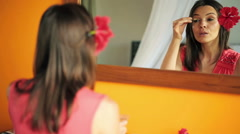 Woman applying makeup, eyeshadow in front of the mirror HD Stock Footage