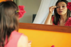 Woman applying makeup, eyeshadow in front of the mirror NTSC Stock Footage