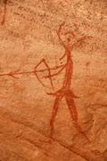 neolithic rock drawing of a human with bow and arrow and an animals head acac - stock photo