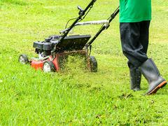 worker mowing grass - stock photo