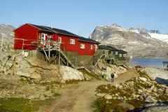 colourful houses made of wood built on solid rock fjord mountain and glaciers - stock photo