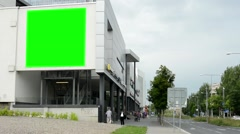 billboard on a building (shopping center) - green screen - street with people - stock footage