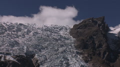 Glacier tumbles steeply, small white cloud, deep blue sky Stock Footage
