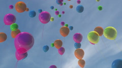 Multi-colored balloons floating in a blue sky - stock footage