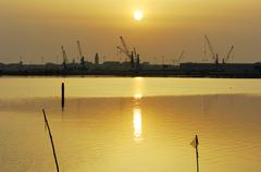 Port of chioggia with cranes at sunrise, the rising sun is reflected in the w Kuvituskuvat