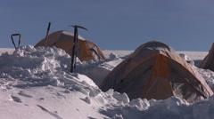 Orange tents dug in on glacier Stock Footage