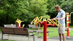 Senior park (exercise machines) with benches - in the park - man strengthens Stock Footage