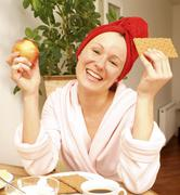 Young woman at substantial breakfast Stock Photos