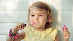 A little girl puts lip balm on her mouth. Children Imitating Adults - stock footage