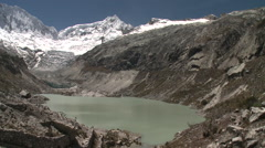 Melt water lake, glacier, mountain peaks blue skies Stock Footage