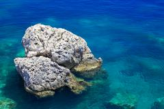 Rock in the turquoise-blue sea, island hvar, dalmatia, croatia Stock Photos