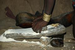 hands of a woman of the hamar people grinding corn on a stone turmi ethiopia - stock photo