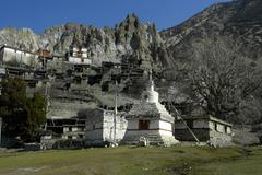 Nested village below rocks and old braga gompa annapurna region nepal Stock Photos