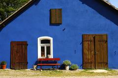 blue house with white-framed window - stock photo