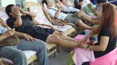 Thai masseur doing leg massage outdoors at the famous backpackers destination Stock Footage