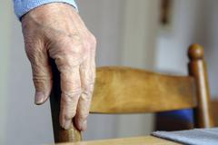 Hand of an old woman on a chair armrest Stock Photos